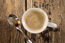 Eine Tasse Espresso mit Löffel und Kaffeebohnen auf Holzuntergrund