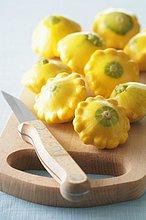 Mehrere gelbe Patissons auf Schneidebrett mit Messer