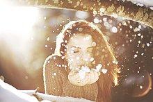 Portrait einer jungen Frau im Schnee bei Gegenlicht