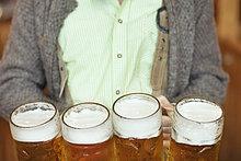 Kellner trägt 4 Maß Bierkrüge auf dem Oktoberfest, München, Deutschland