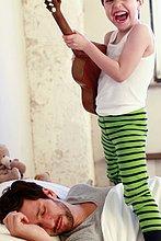 Menschlicher Vater ,Sohn ,schlafen ,Gitarre ,multitasking ,spielen