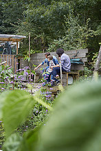 Two men and boy sitting on allotment bench