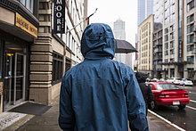 Vereinigte Staaten von Amerika,USA,spazierengehen,spazieren gehen,Mann,Straße,Regen,Rückansicht,Ansicht,jung