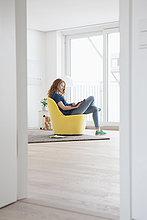 sitzend,junge Frau,junge Frauen,Zimmer,gelb,Sessel,Wohnzimmer