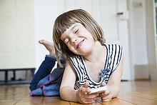 liegend,liegen,liegt,liegendes,liegender,liegende,daliegen,lächeln,klein,Holzboden,Mädchen,Smartphone