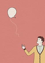 Mann lässt eine Sprechblasen-Luftballon fliegen