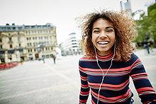 Portrait einer fröhlichen jungen Frau mit Ohrhörern