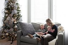 Mutter und Kinder sitzen auf dem Sofa und schauen auf Buch
