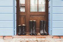 Drei Paar Gummistiefel vor der Haustür