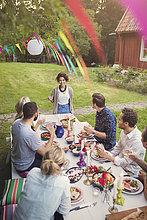 Glückliche Frau im Gespräch mit Freunden am Tisch im Garten Party