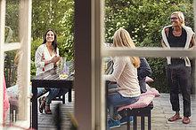 Frauen und Teenager-Mädchen am Esstisch aus Fenster gesehen