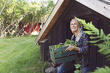 Lächelnde Frau mit Gemüse Kiste beim Kommen aus der Hütte