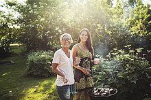 Portrait der glücklichen Frauen stehend von Barbecue-Grill am Hinterhof am sonnigen Tag