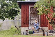 Lächelnde Frau mit Bio-Gemüse sitzen außerhalb Holzhütte
