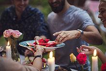Freigestellte Bild der Frau serviert Wassermelone Scheiben zu Freunden bei Garten Party
