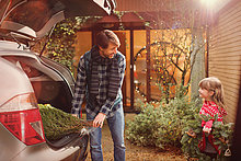 Vater und Tochter entladen Weihnachtsbaum aus dem Auto außerhalb des Hauses