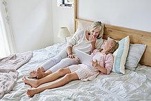Kleines Mädchen liegt auf dem Bett mit ihrer Großmutter mit Tablette