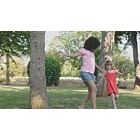 Girl chasing friend around a tree