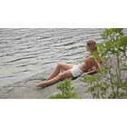 Woman relaxing on rock by lake