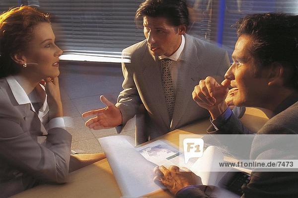 Drei Businesspeople in Meeting diskutieren