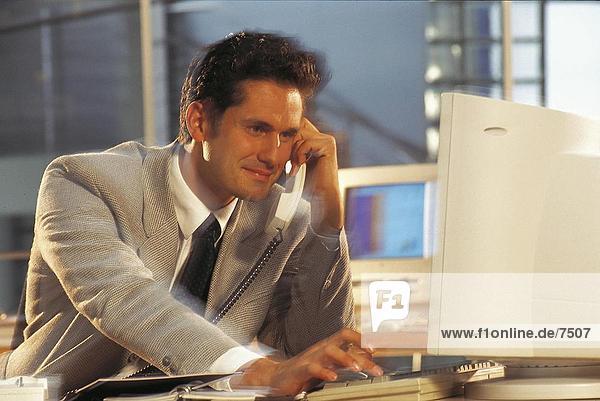 Kaufmann redend über Festnetz-Telefon während der Arbeit an Computer im Büro