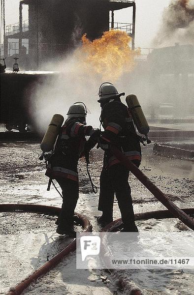 Rückansicht des zwei Feuerwehrleute Sprühen Wasser auf Schieneneinheit  Niederlande