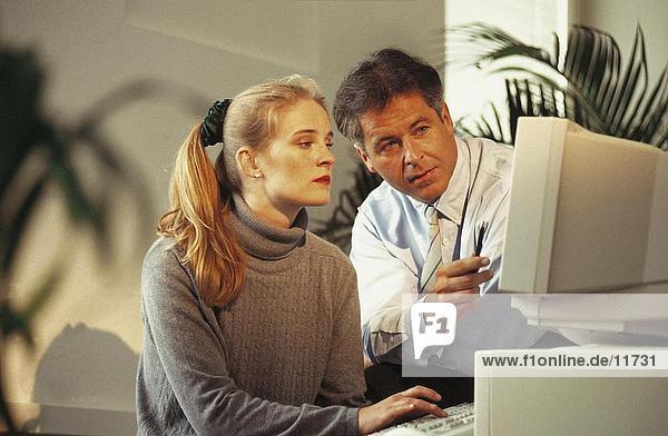 Kaufmann und eine geschäftsfrau  Blick auf Computer-monitor