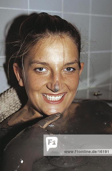 Portrait einer Frau lächelnd in ein Schlammbad
