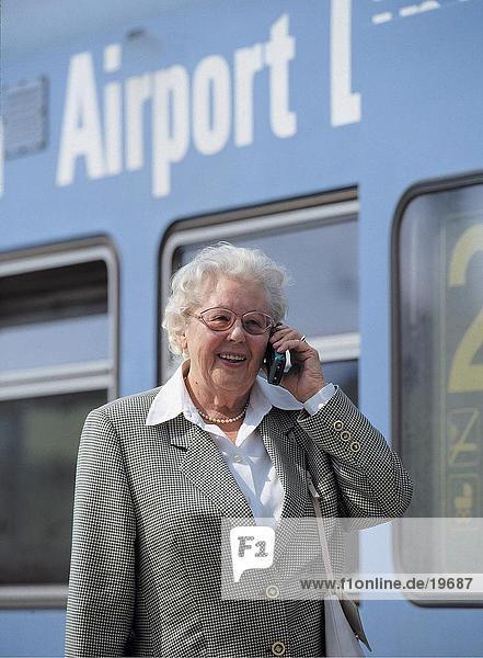 ältere Frau sprechen auf einem Mobiltelefon am Bahnhof