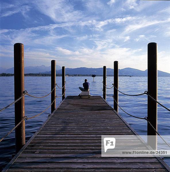 Man sitzt auf Pier am Seeufer  Bodensee  Vorarlberg  Österreich Man sitzt auf Pier am Seeufer, Bodensee, Vorarlberg, Österreich