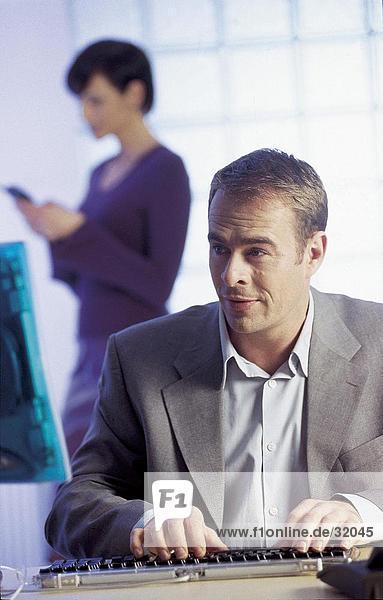 Arbeiten auf einem Computer mit ständigen im Hintergrund geschäftsfrau kaufmann