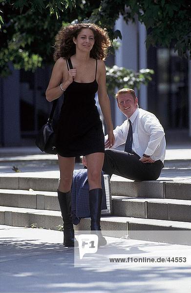Junger Mann Blick auf junge Frau zu Fuß auf der Straße