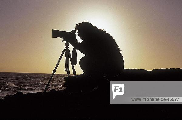 Silhouette der weiblichen Fotograf bei Sonnenuntergang  Australien