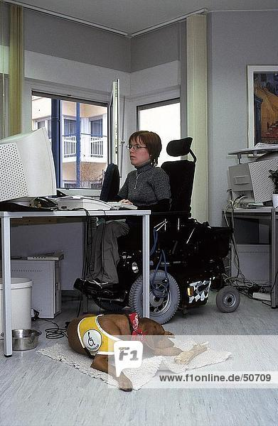 Dog lying in front of handicapped woman working on computer