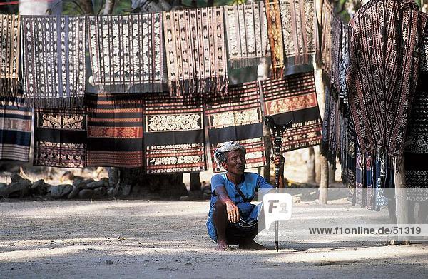 Mann hockend an Ikat Tücher  Sawu Island  Indonesien
