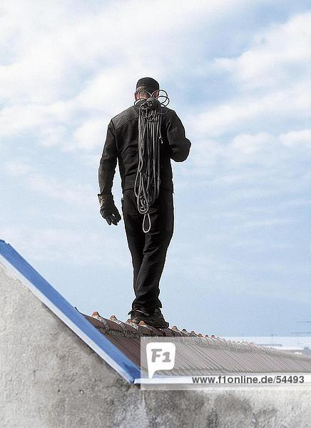 Rear view of man walking on roof