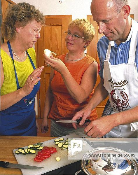 Two women and man preparing food in kitchen