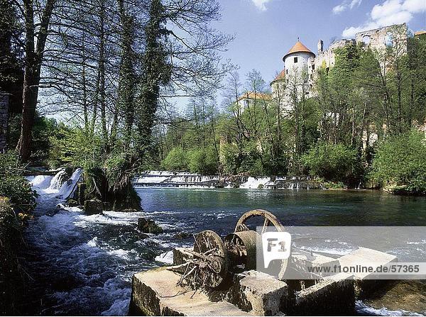 Broken Wassermühle in einem Fluss mit einer Burg im Hintergrund  Slowenien