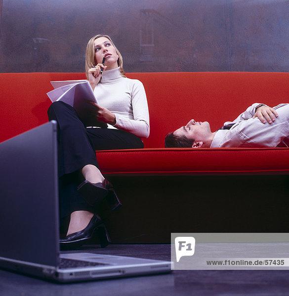Geschäftsfrau Denken mit Geschäftsmann auf Couch schlafend