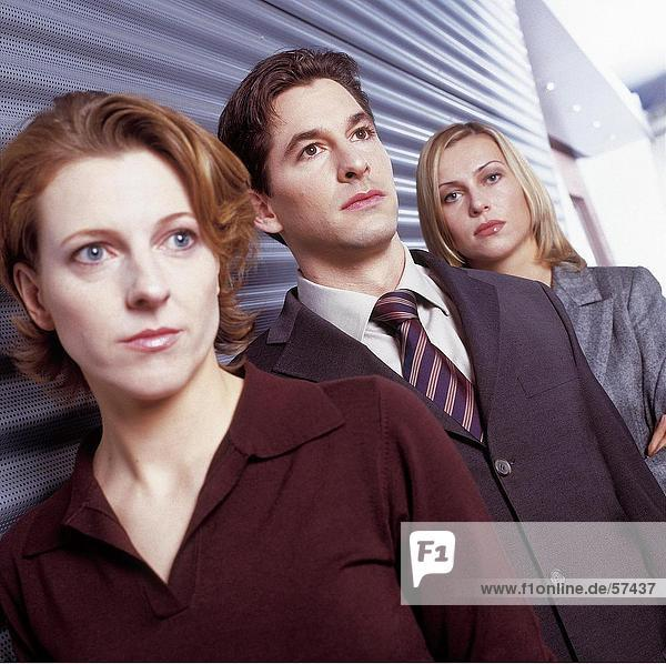 Close-up of two businesswomen and businessman standing in row