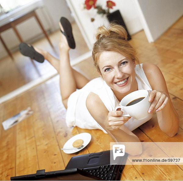 Frau auf Boden liegen und trinken Kaffee  Untersicht