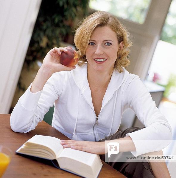 Portrait einer jungen Frau hält eines Pfirsiches und lächelnd