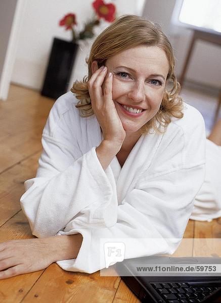 Portrait einer jungen Frau auf Boden liegend mit laptop