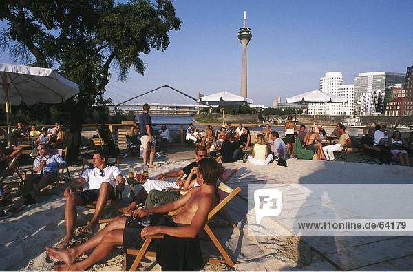 Entspannende Touristen am Strand  Rheinturm Düsseldorf  Düsseldorf  Nordrhein-Westfalen  Deutschland