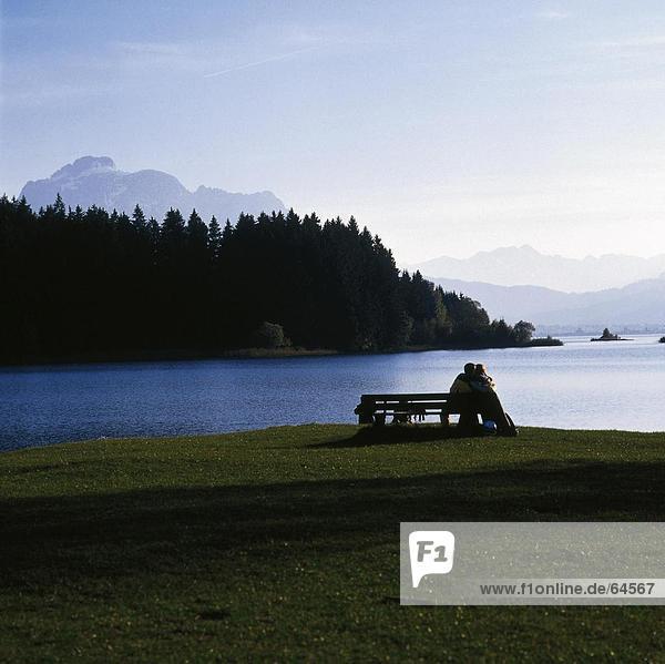 Rückansicht des Paares sitzen auf Bank am Seeufer  Bayern  Deutschland