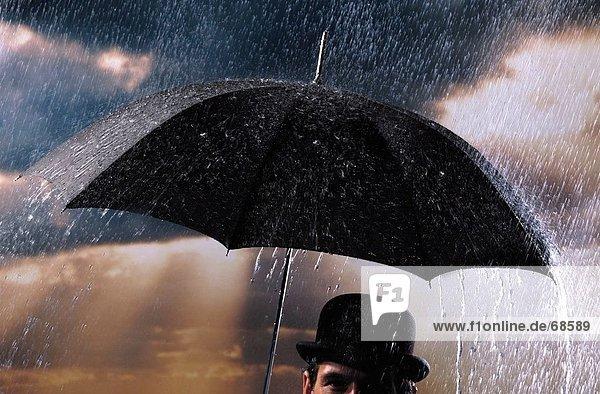 Nahaufnahme der Mann  der Regenschirm hält Nahaufnahme der Mann, der Regenschirm hält