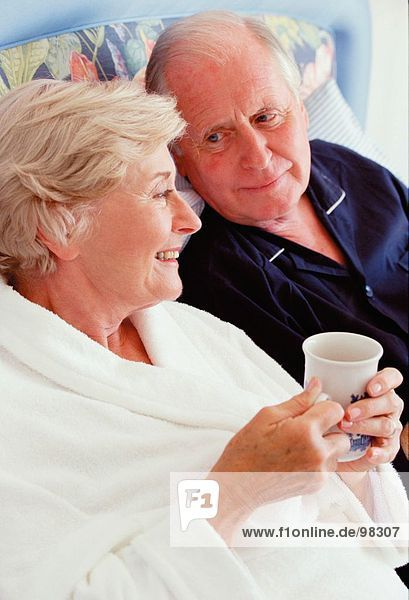 Senior couple indoors in bathrobes. Relaxing with hot drink.