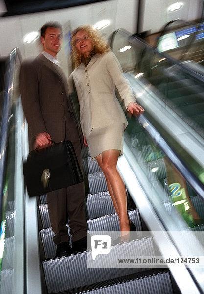 Geschäftspaar auf Rolltreppe