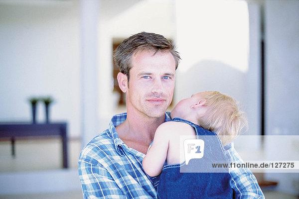 Baby schläft in den Armen des Vaters