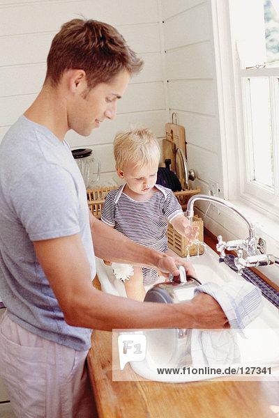 Vater beim Abwasch und Kind beim Spielen mit Wasser